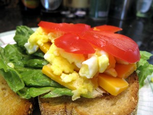 Cover the cheese with scrambled egg and cap with tomatoes