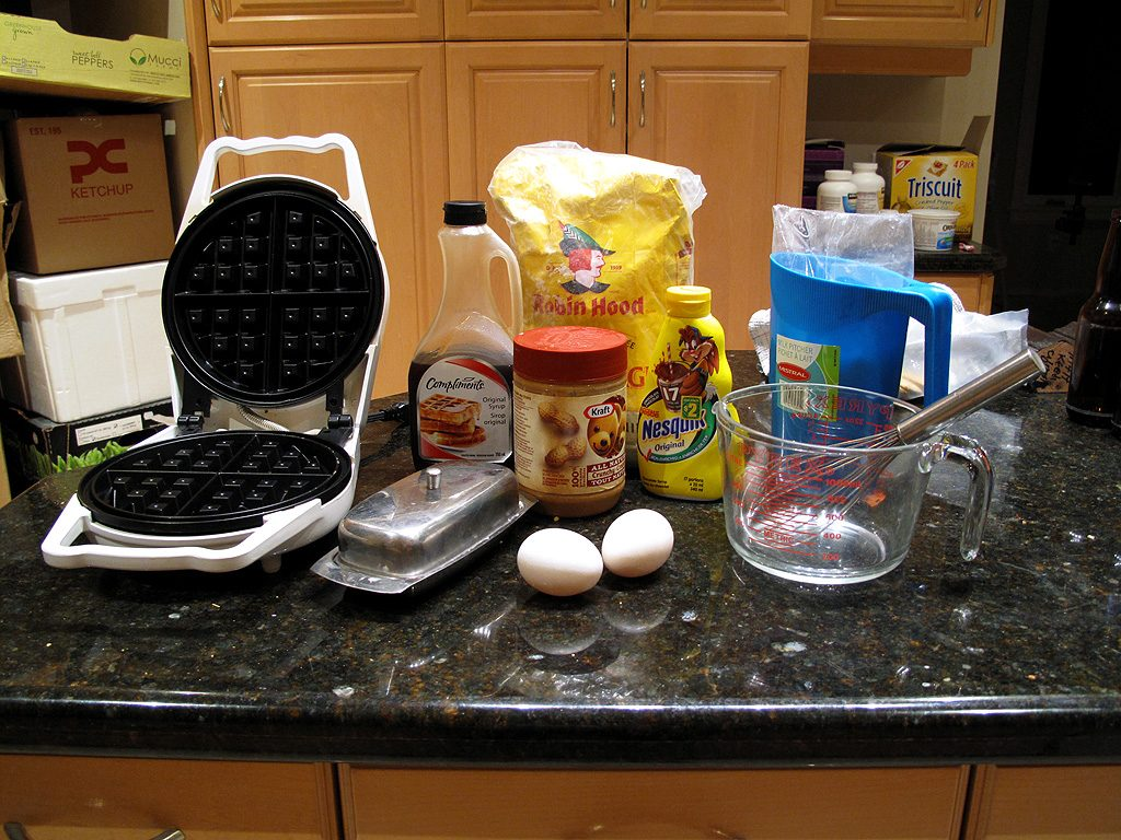 Everything needed to prepare a Belgian Waffle: eggs, milk, butter, flour, baking powder, peanut butter, chocolate sauce, maple syrop, and a waffle iron.