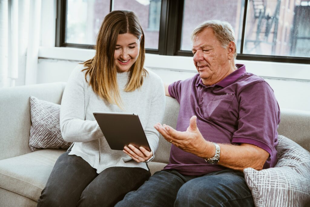 daughter teaching her older father how to use a tablet