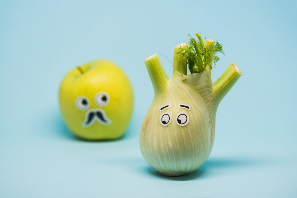 an apple and a lemon decorated with googly eyes