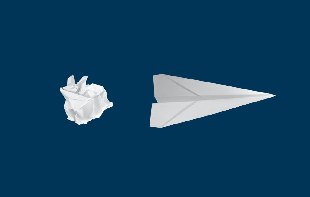 a paper ball next to a paper plane