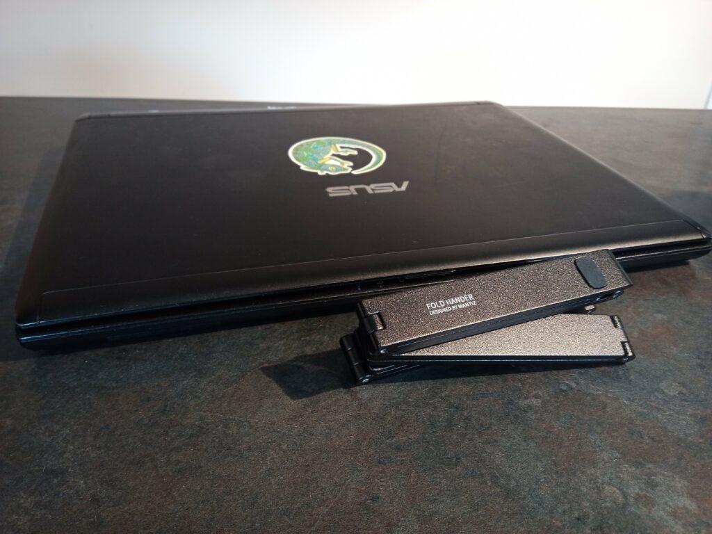 Mantiz stand folded next to a laptop.