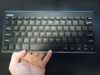 A hand holding a compact keyboard over a desk.